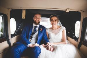 Happy couple in wedding car